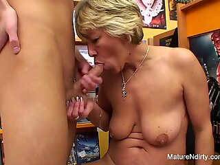 Sexy blonde mature fucks him in the video store